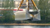 Excavator bucket is gaining the rubble from iron container on the background of the river video