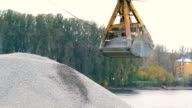 Excavator bucket pours a mountain of rubble on the background of the river video