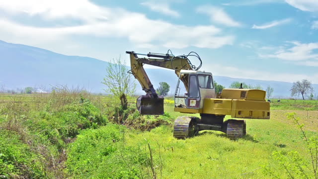 Excavator bulldozer digs infield with raising bucket over cloudscape sky video