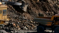 Excavator loads a stone in the heavy truck in the quarry mining granite video