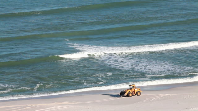 Excavator moves along beach after oil spill video