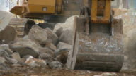 Excavator moving large rocks video
