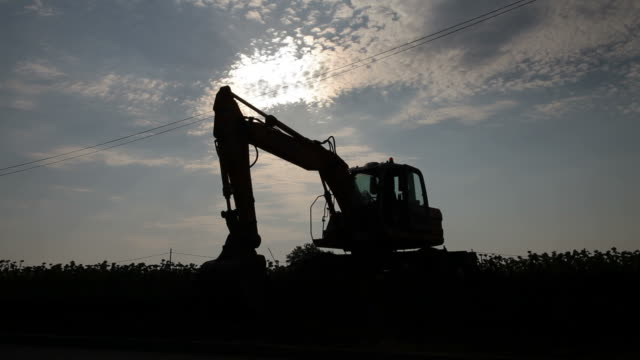 Excavator silhouette working at field video