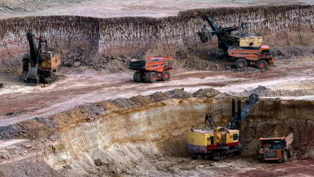 Excavators load ore into dump-trucks. This area has been mined for buaxite, aluminum and other minerals. Open-cast. Operating mine. Bauxite quarry. video