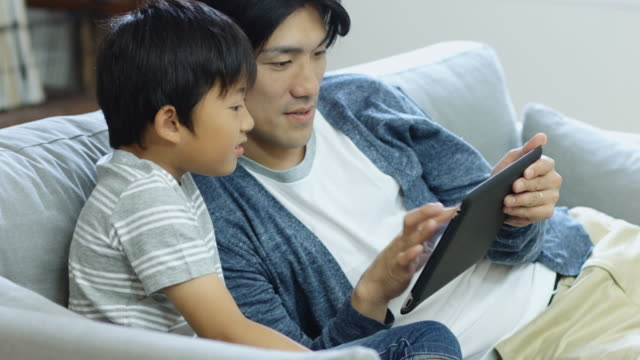 Excited Boy Watching Father Play Game on Tablet video