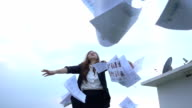 Excited businesswoman throwing papers in the air video