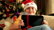 Excited child posing with Christmas gift video