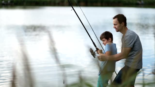 Excited father and son pulling fish out from lake video