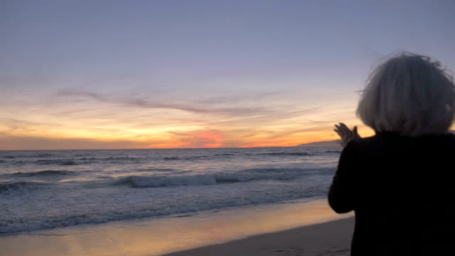 Excited happy retired fit active 60s woman clapping and enjoying sunset on beach video