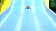 SLOW MOTION: Excited man smiling and sliding down the fast extreme water slide toboggan in aqua park on a beautiful summer day video