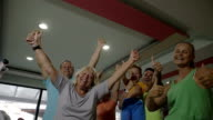 Excited sporty family with thumbs-up in the gym video