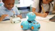 Excited STEM elementary school students test robots in technology class video