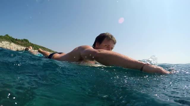 SLOW MOTION UNDERWATER: Excited surfer man paddling on surf in open water ocean video