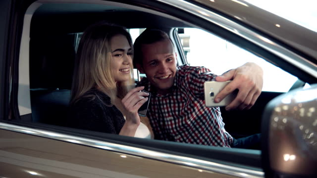 Excited young couple buying a new car and make selfie video