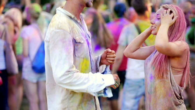 Excited young man and woman covered in Holi colors, dancing in crowd at concert video
