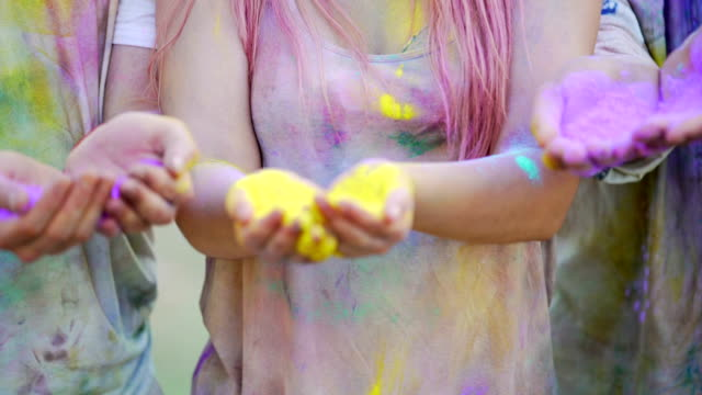 Excited young people throwing coloured powder in air, shining with happiness video