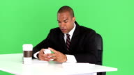 Executive at desk with laptop and talking on cell phone video