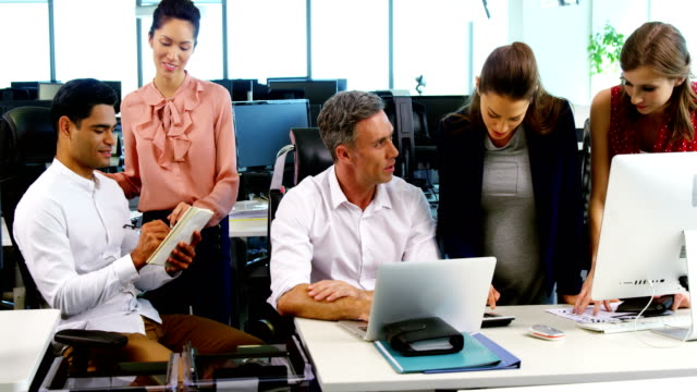 Executives interacting with each other at desk in office video