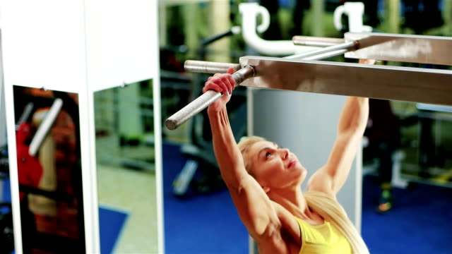 exercises on the horizontal bar, the girl performs a pulling up exercise, athletic woman at the gym, playing sports as a lifestyle, a healthy strong body video