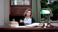 Exhausted female fallen asleep on the stack of books at her desk and woken up by an alarm quickly takes her books and papers, drinks coffee and leaves video