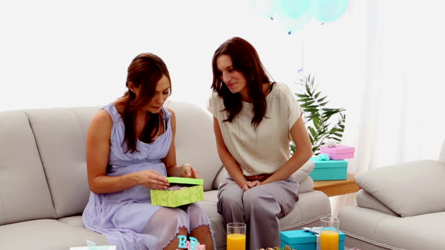 Expectant mother receiving present from friend video