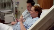 Expecting Couple Playing With Digital Tablet In Hospital Room video