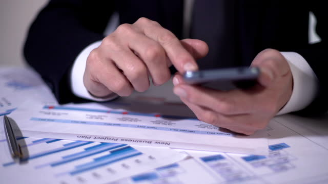 Experienced businessman using mobile app on gadget, planning business project video