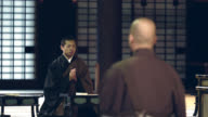 Experienced monks and young monk praying in Japanese temple video