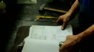 expert checks the item after the repair on workplace, opens recording details and scrolls the magazine in his hands detail on the table are a number of locksmith tools video