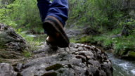 explorer is walking on a rocky path by the river - back view video