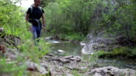 explorer is walking on a rocky path by the river - front view video