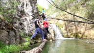explorers crossing river on a log and climbing on rock video