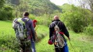 explorers hiking and going to climb mountain top video