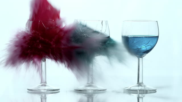 SLO MO explosion of wine glasses filled with colored liquid video