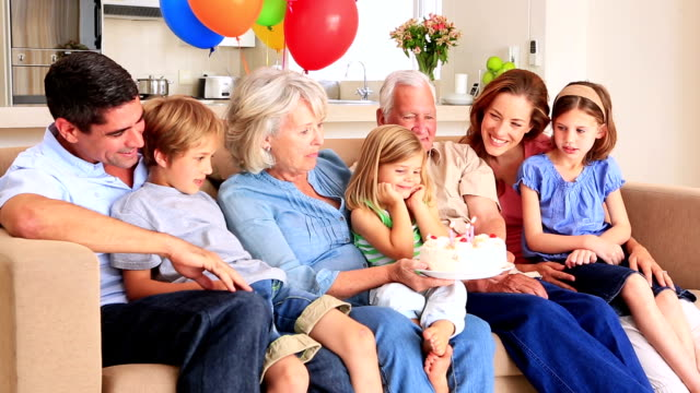 Extended family celebrating birthday together on couch video