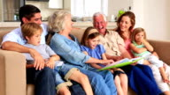 Extended family looking at photo album together on couch video