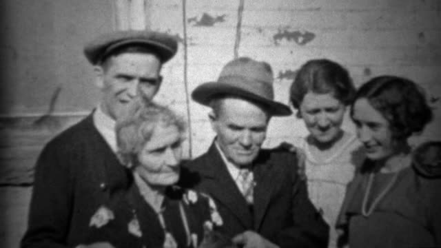 1933: Extended family petting family car outside of depression era home. video