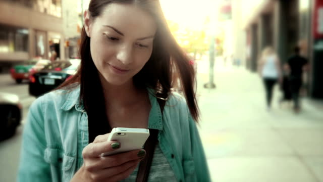 Exterior shot of a pretty woman texting on her cellphone video