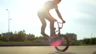 SLOW MOTION: Extreme bmx biker doing cool tail whip tricks in city at sunset video