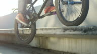 SLOW MOTION CLOSEUP: Extreme bmx biker jumping on bench and doing peg grid trick video