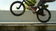 SLOW MOTION CLOSE UP: Extreme bmx biker jumping on bench and doing wheelie trick video