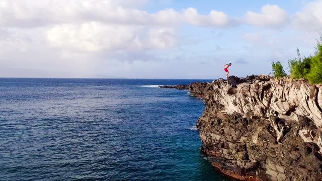 Extreme Cliff Jumping Backflip. Aerial View Cliff Jumping into Blue Ocean. video