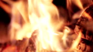 Extreme close up logs wood burning in outdoor camp fire on dark black background with spurts of flame and lots of sparks video