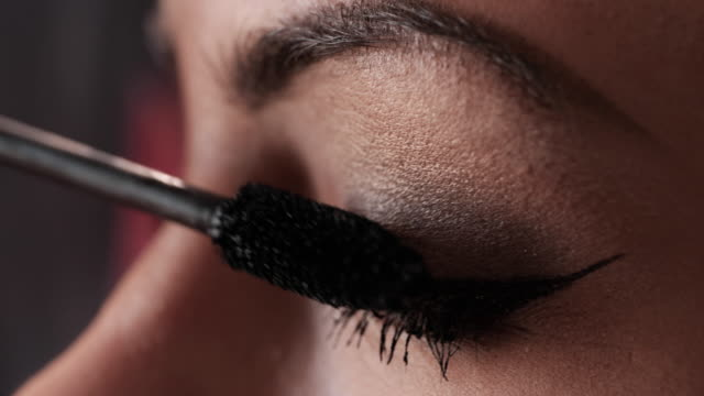 Extreme close up of a woman applying mascara on eyelashes. video