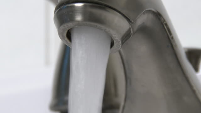 Extreme close up, water faucet being turned on and off, full stream, in 4K video