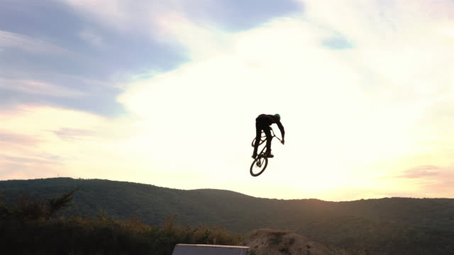Extreme cyclist jumping over sports ramp and backflipping over dirt hills at sunset. video