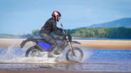 Extreme driving a motorcycle. A skilled biker riding on the edge of water video