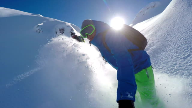 Extreme freeride snowboarders riding powder snow backcountry in snowy mountains video