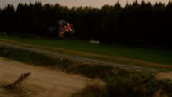 AERIAL SLOW MOTION: Extreme motocross biker jumping no footer trick at sunset video