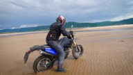 Extreme motorcyclist rides on sandy bank of the river video